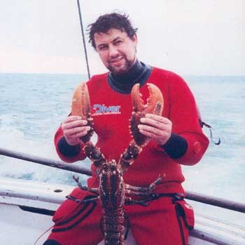 Image of Skipper Mike Keane holding lobster found during a dive